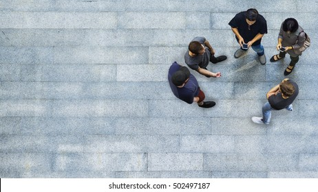 top view group of people are playing and talking with the smart phone on the concrete pedestrian (Aerial view)