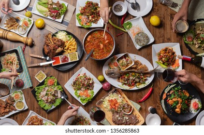 Top view, Group of people sitting at the wooden table with Steak, Fish, Vegetables and Spices,Thai food
