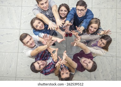 Top view of group of people. Standing together, raising their hands up.