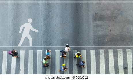 the top view of group people walk on crosswalk pedestrian walkway with the white signage symbol of people walk on the road