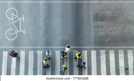 the top view of group people walk on crosswalk pedestrian walkway with the white signage symbol of bicycle on the road