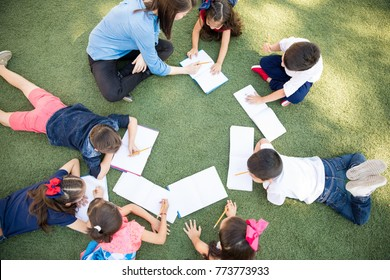 Top view of a group of preschool students and their teacher lying on the grass and taking a class outdoors
