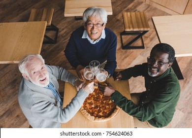 top view of group of senior friends clinking glasses of beer in bar with pizza on table