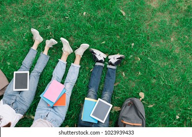 Top view of group of students university sitting relaxed in a park on a green grass with a laptop, a notebook and a book on the leg.