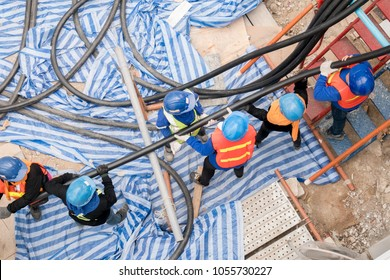 Top view group of teamwork electrician workers installing industrial cable in factory utility building