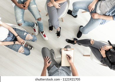 Top view of a group therapy session for teenagers struggling with depression