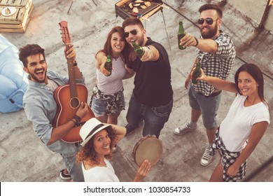 Top view of a group of young friends having fun at a rooftop party, playing the guitar, singing and enjoying hot summer days. Focus on the couple in the middle