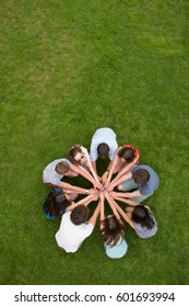 Top view. Group of young people outside, they form a circle and join their hands in the center