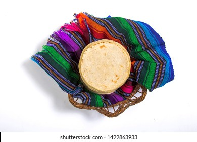 Top view of guatemalan handmade corn tortillas inside a basket covered by traditional textiles isolated on white background