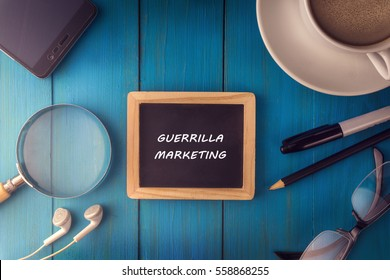 Top view of GUERRILLA MARKETING written on the chalkboard,business concept.chalkboard,smart phone,cup,magnifier glass,glasses pen on wooden desk.