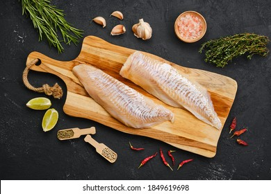 Top view of haddock fillet with seasoning on wooden cutting board