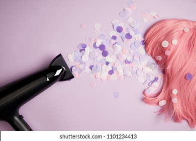 top view of hair dryer, confetti and pink wig on purple