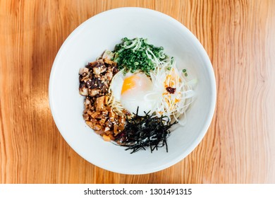 Top view of Hakata style Mazesoba: Dry ramen with Chasiu bits, spring onions, bamboo shoots, chilli oil, leeks, sesame seeds and onsen egg.