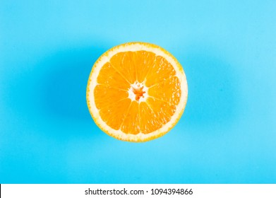 Top view of a half orange fruit on blue colored background