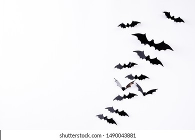 Top view of Halloween crafts, black paper bats flying over white background with copy space for text. halloween concept.