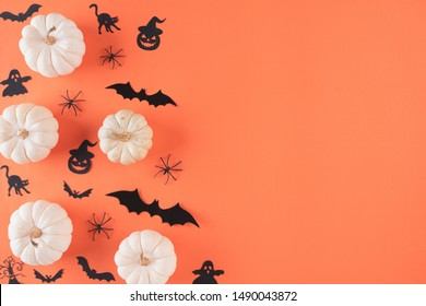 Top view of Halloween crafts, white pumpkin, ghost, bat and spider on orange background with copy space for text. halloween concept.