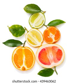 Top view of halves citrus fruits (orange, lime, grapefruit, clementine and lemon) with green leaves isolated on white background.