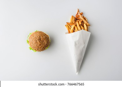 top view of hamburger and french fries in paper cone, isolated on white