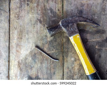 Top view of hammer and nail on wooden background