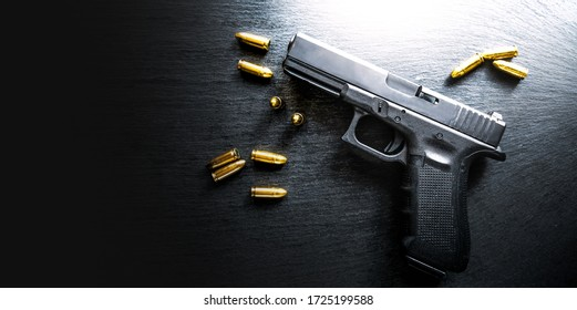 Top view of hand gun on black background with bullets around. 9mm pistol with ammunition on dark table.