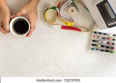 top view of hand holding coffee cup with accessory for sewing. break time for relax. fashion business concept