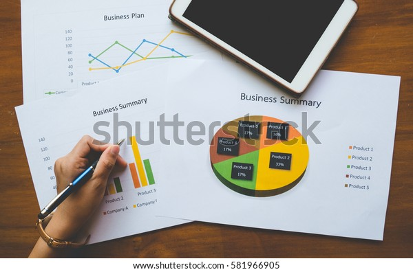 Top - view of  hand holding pen with Business summary or Business plan report with Charts and graphs in Business concept, vintage style