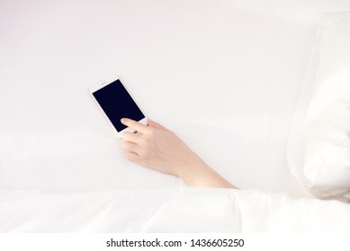 Top view hand holding using mobile phone.girl using smart phone on the bed.