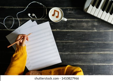 Top view hand of musician holding pencil to compost a song on blank staff notation sheet over black painted wood table with white cup of coffee with musical note symbol on frothy surface and keyboard.