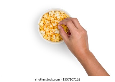 Top view of The hand is picking a popcorn coated with golden yellow caramel looks tasty on white background with clipping path.
