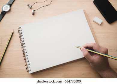 Top view of a hand taking down note in a personal notebook. Business man is writing in a diary on wooden table. Blank page to write your own message.