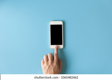 Top view of  hand touching smartphone on the blue pastel color background.