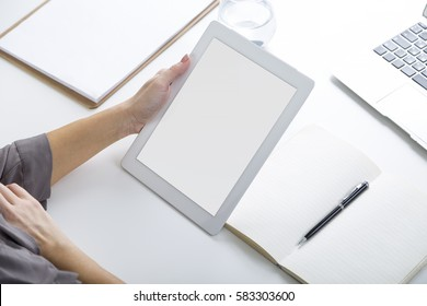 Top view of a hand of a woman holding a tablet computer with a blank screen. There is a laptop, a clipboard and an open notebook on the desk. Mock up.