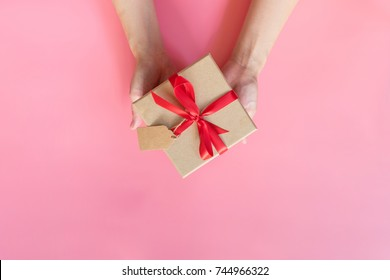 top view hand woman holding brown gift box for new year on pink pastel color background with space.