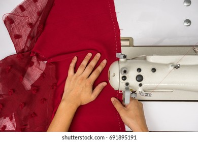 top view of hand working with sewing machine and red fabric