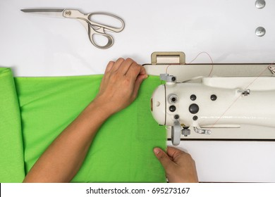 top view of hand working with sewing machine and green fabric