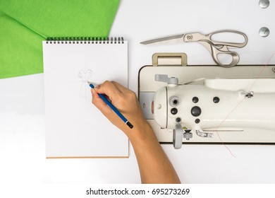top view of hand writing in notebook for design about dress with sewing machine