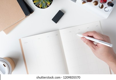 top view of hand writing on open calendar planner for business resolution with modern office stationery and take away coffee cup on white desk in office.mock up space of organizer table notebook