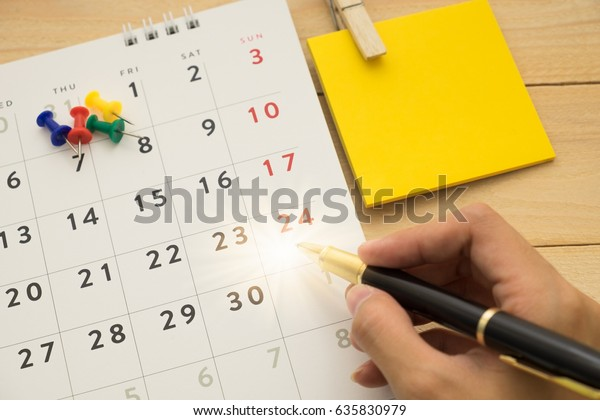 top view. hand of young woman using pen writing on desktop calendar and have yellow post-it note putting on beside them. wooden are background. this image for business accessory concept