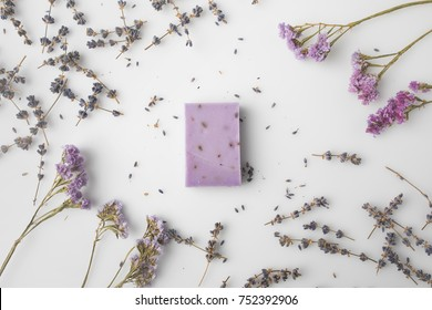 top view of handcrafted purple lavender soap with flowers around on white surface