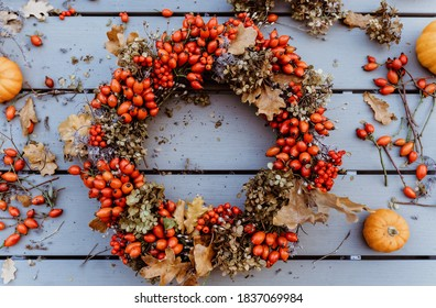 Top view of handmade colorful floral autumn door wreath made of colorful rosehip berries, rowan, dry flowers and oak leaves. Fall flower decoration workshop..