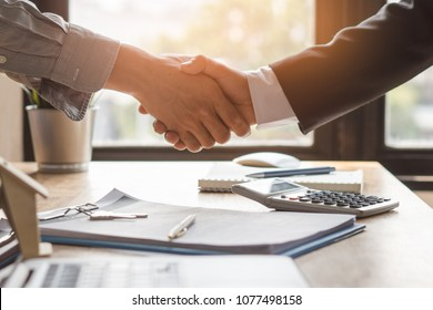 Top view hands of agent and client shaking hands after signed contract buy new apartment.
