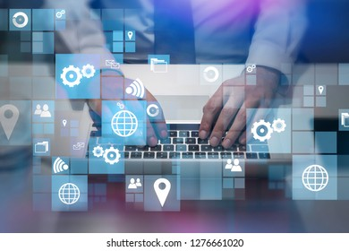 Top view of hands of businessman typing on laptop keyboard in office with business interface icons in the foreground. Toned image double exposure