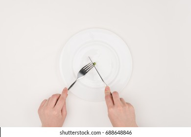 top view of hands cutting pea with knife and fork isolated on white