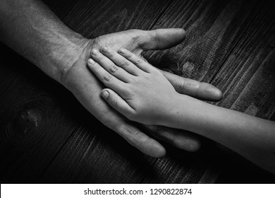 Top view, Hands of an elderly man holding the hand of a younger man. Lots of texture and character in the old man hands. on black wooden background.black and white.
