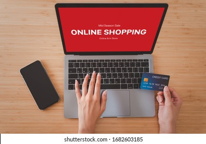 Top view hands holding credit card and use for shopping payment online on laptop, shopping online concept.