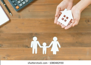 Top view of hands holding family and house paper with calculator and notebook