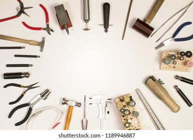Top view of hands holding goldsmiths tools, jewelry objects. Tools over white background.