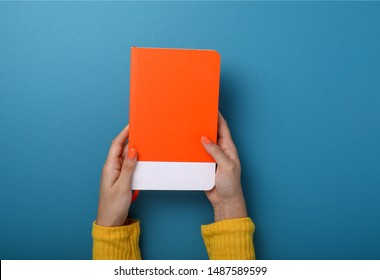 Top view of hands holding an orange notebook over blue background.