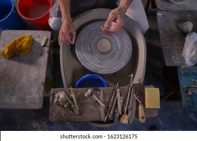 Top view of hands male sculpts new earthenware with tools and water. Man's fingers work with clay on the potter wheel.