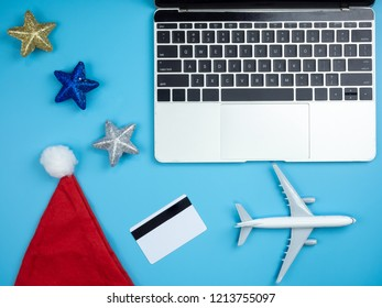 Top view of hands on laptop , smartphone , Santa hat, credit card, plane and Christmas ornament on blue isolated background with copy space.